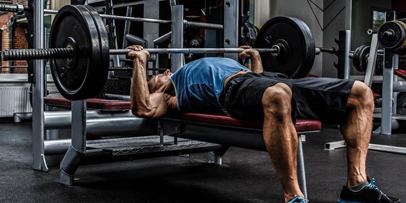 Man leaning on bench press machine Free Photo