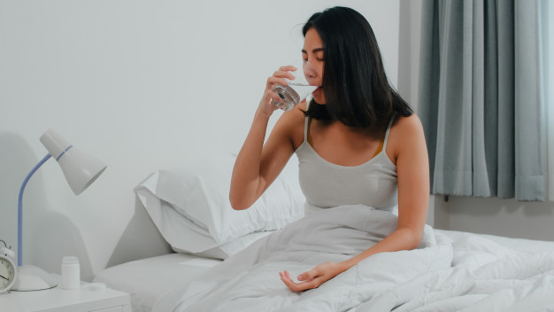 unhealthy-sick-indian-female-suffers-from-insomnia-asian-young-woman-taking-painkiller-medicine-relieve-headache-pain-drink-glass-water-sitting-bed-her-bedroom-home-morning
